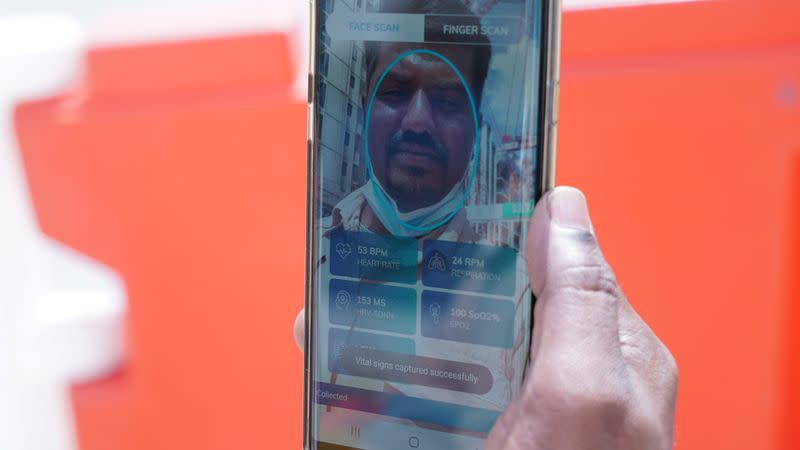 Kajima employee Gunasekar Udayakumar uses the Nervotec app to scan his face and check his vital signs as part of a daily checkup for employees at a construction site in central Singapore