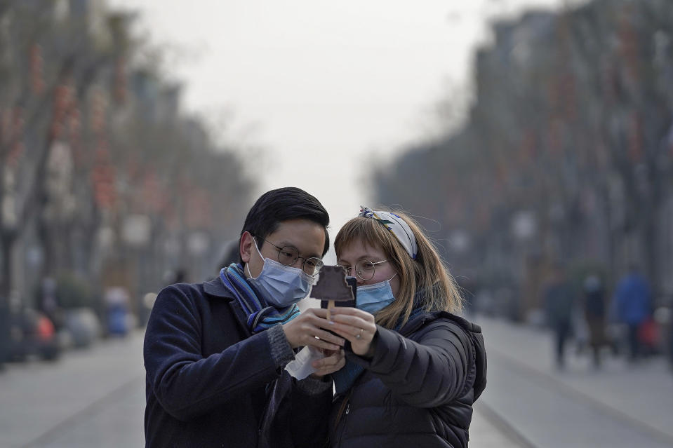 Visitors wearing face masks to help curb the spread of the coronavirus take a smartphone photo of an ice-cream with a shaped of Qianmen Gate which bought at Qianmen Street, a popular tourist spot in Beijing, Sunday, Jan. 31, 2021. A World Health Organization team looking into the origins of the coronavirus pandemic on Sunday visited the seafood market in the Chinese city of Wuhan that was linked to many early infections. (AP Photo/Andy Wong)