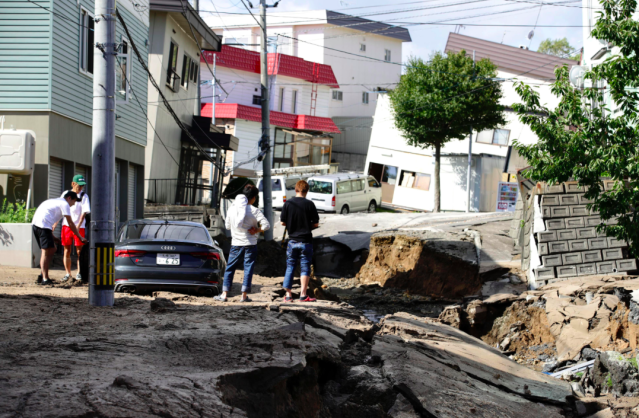 <em>Residents watch a road damaged by the earthquake in Sapporo, Hokkaido (AP)</em>