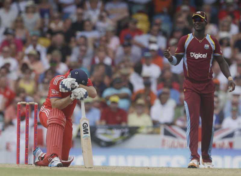 England's Michael Lumb kneels next to West Indies' Darren Sammy during their third T20 International cricket match at the Kensington Oval in Bridgetown, Barbados, Thursday, March 13, 2014. (AP Photo/Ricardo Mazalan)