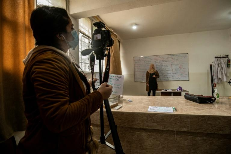 A colleague films a lesson by Kurdish language teacher Hayat Abbas to be broadcast on local televion and Youtube for distance learning, in the Kurdish-majority city of Qamishli in Syria's northeastern Hasakeh province (AFP Photo/Delil SOULEIMAN)