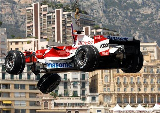 The wreck of German formula one driver Ralf Schumacher's Toyota is lifted up in front of the buildings of Monaco Thursday May 24, 2007. Schumacher crashed during the second free practice session for Sunday's Monaco Grand Prix. (AP Photo/ Claude Paris)