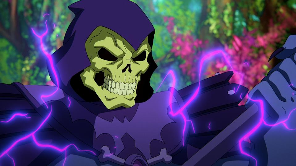 In a CG animated still from Masters of the Universe: Revelation, Skeletor, who wears a purple cloak and hood over his skull, stands in a forest with bright foliage as he grips his spear as purple electricity sparks around him.