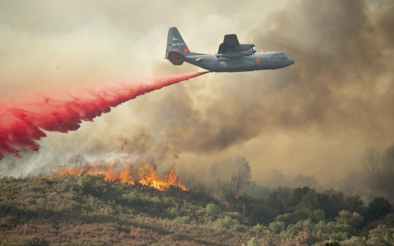 A U.S. Air Force plane drops fire retardant on a burning hillside in the Ranch Fire in Clearlake Oaks, Calif., Sunday, Aug. 5, 2018. (AP Photo/Josh Edelson)