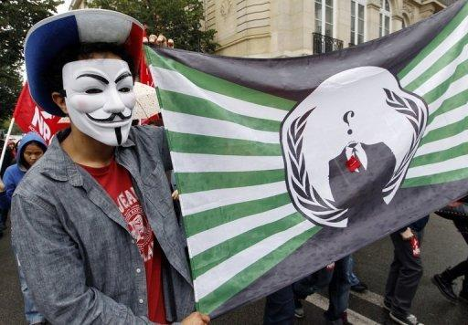 An Anonymous supporter holds a flag bearing the Anonymous logo