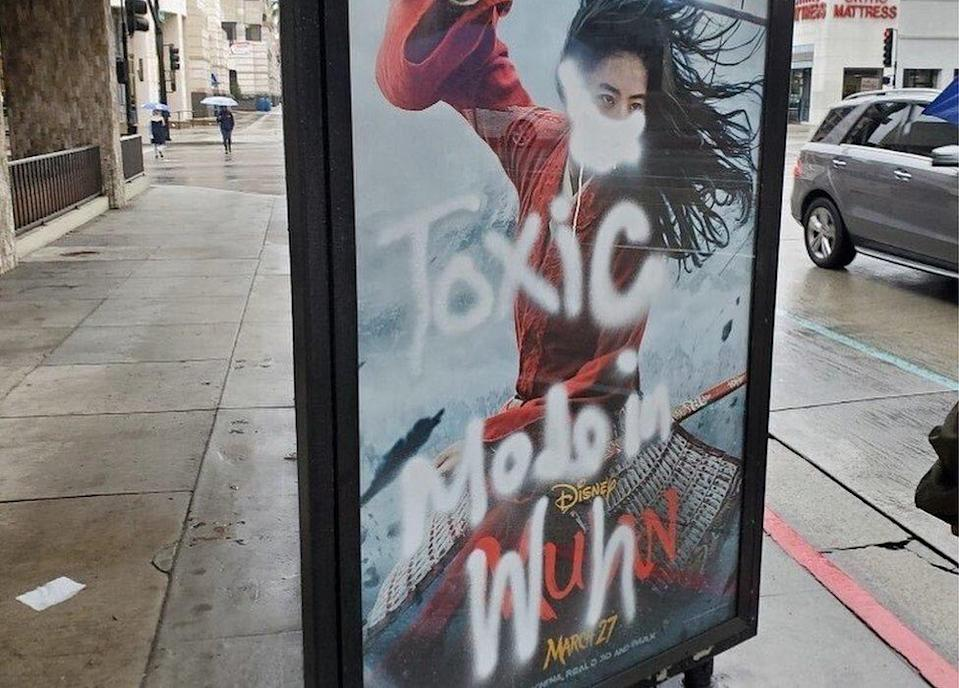 A Mulan film poster defaced with graffiti - a mask is painted over her face, along with the words
