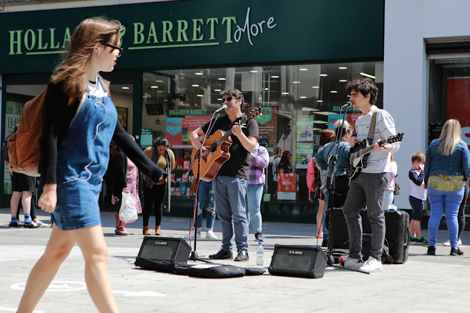 Street performers play music for shoppers as lockdown restrictions have been relaxed to allow non-essential shops to reopen in England