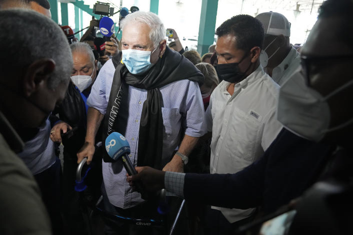 Panama's former President Ricardo Martinelli arrives to court surrounded by press for the start of his trial in Panama City, Wednesday, July 21, 2021. Martinelli faces trial for alleged eavesdropping on political rivals and journalists during his administration, the same case for which he was acquitted in 2018. (AP Photo/Arnulfo Franco)