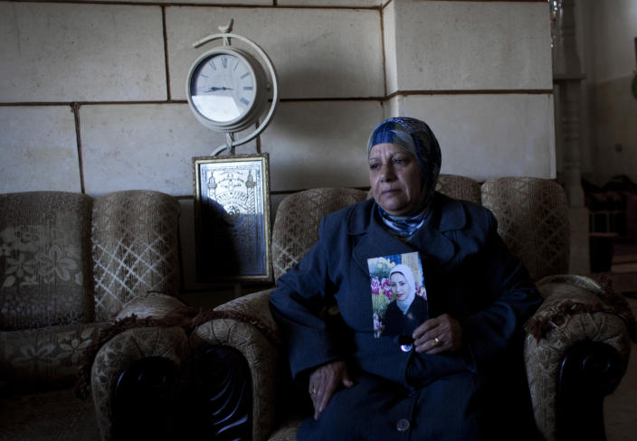 In this photo taken Saturday, Feb. 1, 2014, Palestinian Khadra al-Akhras poses with a photo of her late daughter Ayat al-Akhras, who blew herself up in a suicide bombing outside a Jerusalem supermarket in 2002, at the family house in the West Bank city of Bethlehem. More than a decade later, after appeals from human rights groups, Israel is handing over some 30 bodies of Palestinian assailants, including that of Ayat. (AP Photo/Nasser Nasser)