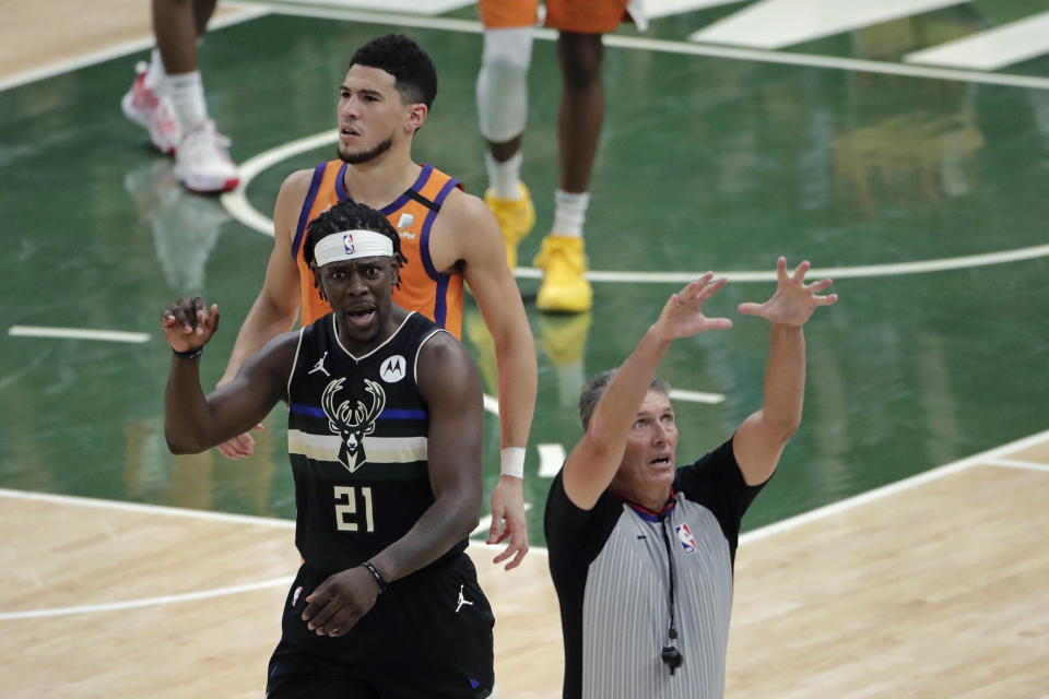 Milwaukee Bucks guard Jrue Holiday (21) reacts in front of Phoenix Suns guard Devin Booker during the first half of Game 6 of basketball's NBA Finals Tuesday, July 20, 2021, in Milwaukee. (AP Photo/Aaron Gash)