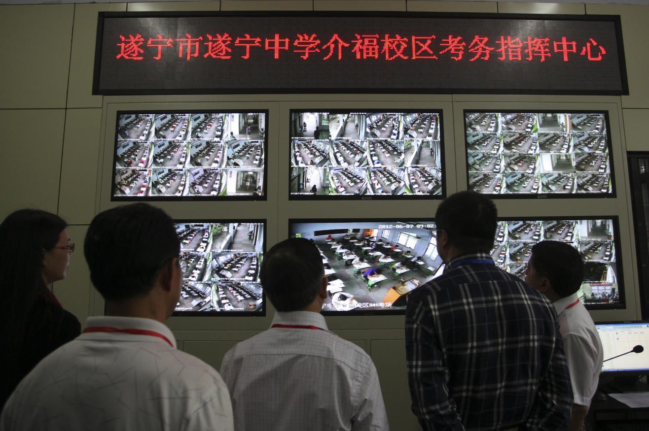 """Invigilators look at monitor screens showing students taking the National College Entrance Exams at a high school in Suining, Sichuan province June 7, 2012. The Chinese characters on the electronic board read """"Suining High School Jiefu Area Examination Monitor Center"""". About three out of four applicants of China's annual national college entrance exam, the largest in the country and the world, will be admitted by universities, with the exam contents highly guarded by armed police and surveillance cameras, Xinhua News Agency reported. REUTERS/Stringer"""