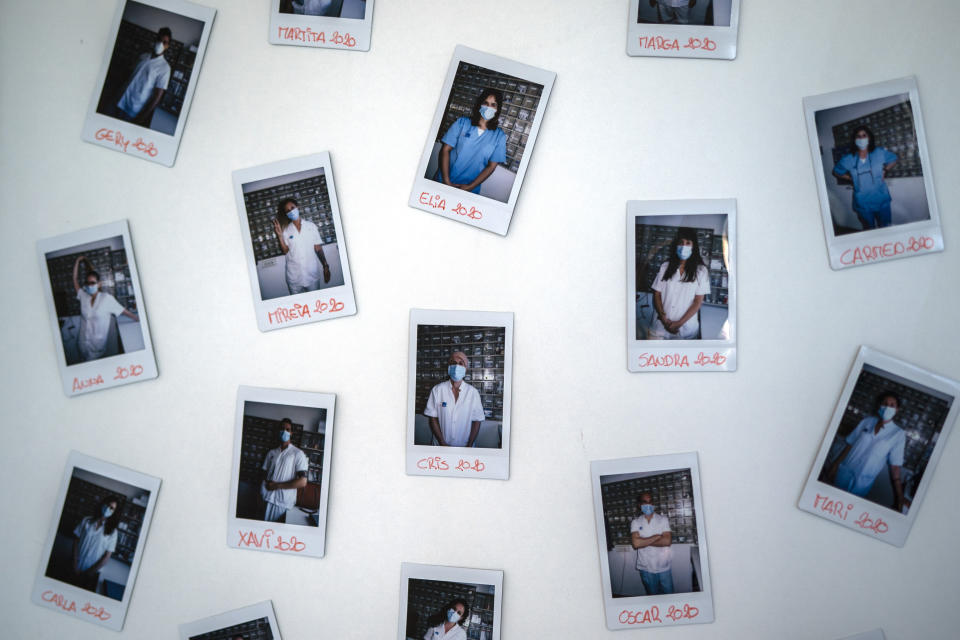 Photos of Nurse Marta Fernandez's co-workers are pictured on the dining room wall of the COVID-19 ward at the hospital del Mar in Barcelona, Spain, Wednesday, Nov. 18, 2020. (AP Photo/Emilio Morenatti)