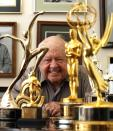Actor Mickey Rooney smiles in front of his trophies during an interview with Reuters at his home in Westlake Village, California in this February 14, 2007 file photo. Rooney, the pint-sized screen dynamo of the 1930s and 1940s best known for his boy-next-door role in the Andy Hardy movies, died on April 6, 2014 at 93, the TMZ celebrity website reported. It did not give a cause of death and a spokesman was not immediately available for comment. REUTERS/Mario Anzuoni/Files (UNITED STATES - Tags: ENTERTAINMENT OBITUARY)