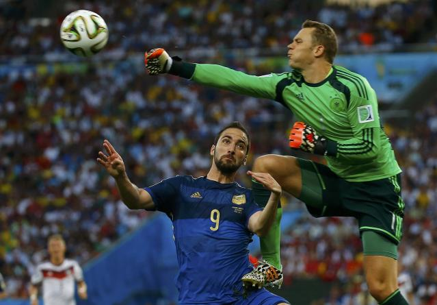 Germany's goalkeeper Manuel Neuer collides into Argentina's Gonzalo Higuain (L) as he clears the ball during their 2014 World Cup final at the Maracana stadium in Rio de Janeiro July 13, 2014. REUTERS/Kai Pfaffenbach (BRAZIL - Tags: SOCCER SPORT WORLD CUP TPX IMAGES OF THE DAY)