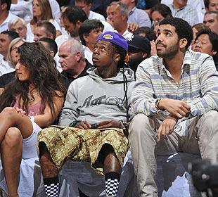 Drake (right) sits with fellow rapper Lil' Wayne (middle) on Tuesday at Game 4 of the East finals