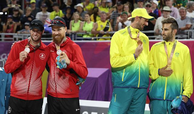 Beach Volleyball - Gold Coast 2018 Commonwealth Games - Men's Medal Ceremony - Coolangatta Beachfront - Gold Coast, Australia - April 12, 2018. Gold medalists Christopher McHugh and Damien Schumann of Australia and silver medalists Samuel Pedlow and Sam Schachter of Canada on the podium. REUTERS/Athit Perawongmetha