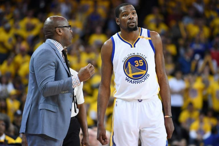 Acting head coach of the Golden State Warriors, Mike Brown, speaks with Kevin Durant during Game One of the NBA Western Conference Finals against the San Antonio Spurs, at ORACLE Arena in Oakland, California, on May 14, 2017