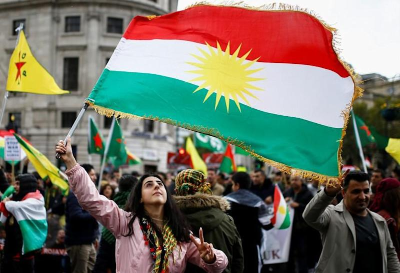 A woman flashes a V-sign as she waves a Kurdish flag during a pro-Kurdish rally against Turkey's military action in northeastern Syria, in London: REUTERS