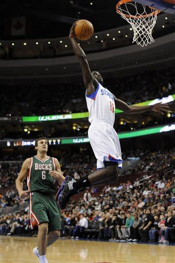 Philadelphia 76ers' Jrue Holiday (11) dunks over Milwaukee Bucks' Andrew Bout (6), of Australia, in the first half of and NBA basketball game on Monday, Jan. 16, 2012, in Philadelphia. (AP Photo/Michael Perez)