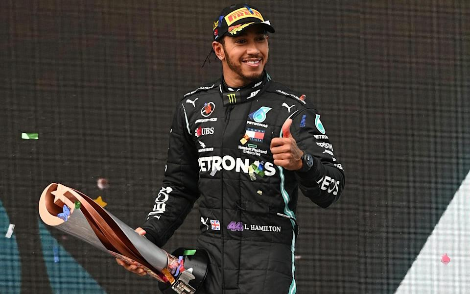 Lewis Hamilton celebrates on the podium with a trophy after winning the race and the world championship -  Pool via REUTERS