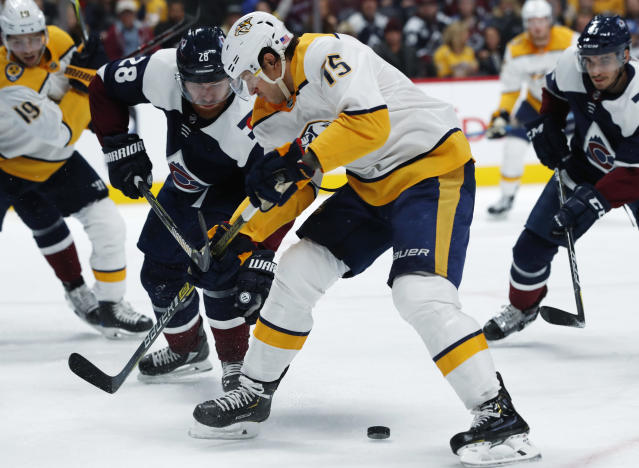 Nashville Predators right wing Craig Smith, right, fights for control of the puck with Colorado Avalanche defenseman Ian Cole during the second period of an NHL hockey game Wednesday, Nov. 7, 2018, in Denver. (AP Photo/David Zalubowski)