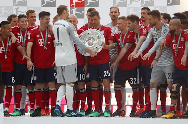 Soccer Football - Bundesliga - Bayern Munich v VfB Stuttgart - Allianz Arena, Munich, Germany - May 12, 2018 Bayern Munich's Manuel Neuer passes the trophy to Thomas Mueller as they celebrate winning the Bundesliga REUTERS/Michael Dalder DFL RULES TO LIMIT THE ONLINE USAGE DURING MATCH TIME TO 15 PICTURES PER GAME. IMAGE SEQUENCES TO SIMULATE VIDEO IS NOT ALLOWED AT ANY TIME. FOR FURTHER QUERIES PLEASE CONTACT DFL DIRECTLY AT + 49 69 650050