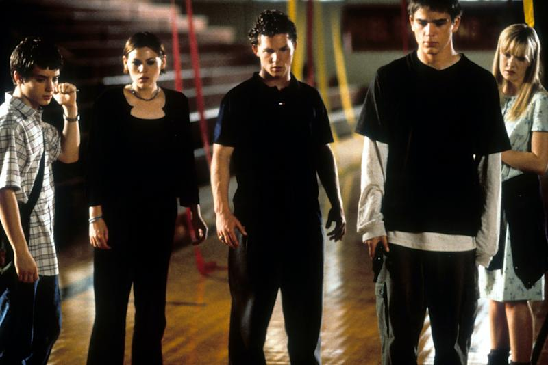 From left to right, Elijah Wood, Clea DuVall, Shawn Hatosy, Josh Hartnett and Laura Harris looking down at the floor with group of peers in a scene from the film 'The Faculty', 1998. (Photo by Buena Vista/Getty Images)
