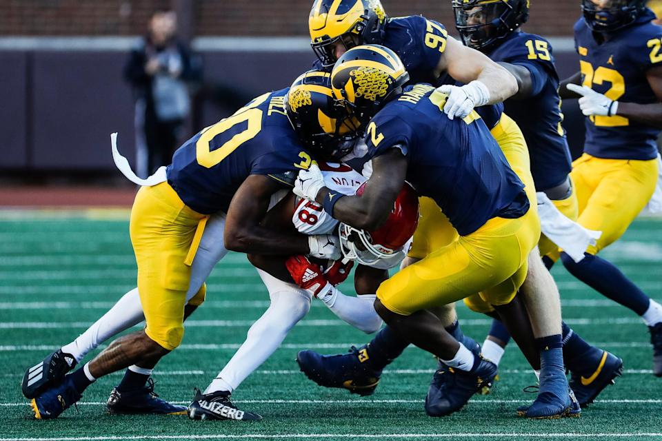 Michigan defensive back Daxton Hill (30) and defensive back Brad Hawkins (2) tackle Rutgers wide receiver Bo Melton (18) during the second half at Michigan Stadium in Ann Arbor on Saturday, Sept. 25, 2021.