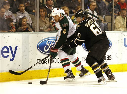 Minnesota Wild defenseman Clayton Stoner,left, (4) and Dallas Stars forward Antoine Roussel (60) fight for the puck during the first period of an NHL hockey game Friday, March 29, 2013, in Dallas, Texas. (AP Photo/Sharon Ellman)