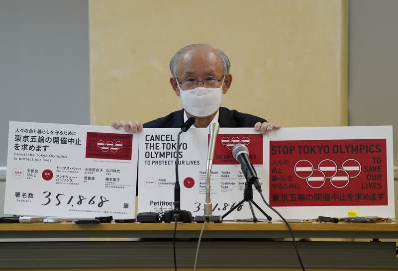 Lawyer Kenji Utsunomiya shows off placards during a news conference after he and anti-Olympics petition organizer to submit a petition calling for the Tokyo 2020 Olympics to be cancelled in Tokyo