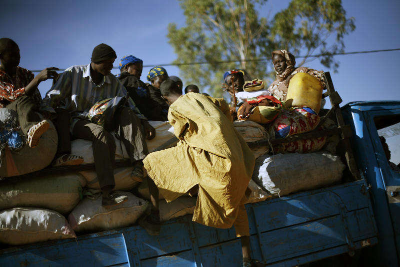 travelers climb back on a transport truck after being checked by Malian soldiers at a checkpoint in Niono, Mali, some 400 kms (300 miles) North of the capital Bamako Saturday Jan. 19, 2013. French troops encircled a key Malian town on Friday, trying to stop radical Islamists from striking against communities closer to the capital and cutting off their supply line, a French official said. The move around Diabaly came as French and Malian authorities said that the city whose capture prompted the French military intervention in the first place was no longer in the hands of the extremists.(AP Photo/Jerome Delay)