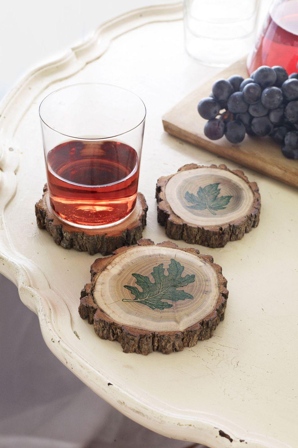 """<p>To make these rustic drink perches, you'll need a <span class=""""redactor-unlink"""">tree limb</span> that's roughly three inches in diameter. Saw the branch into slices about 3/4-inch thick—or have a hardware store do it for you—and lightly sand each wood disk. Create the leaf motifs shown by pressing an inked stamp onto each coaster. Let dry for five minutes, then coat the stamped side with a protective matte finishing spray. Allow 15 minutes of drying time before using.</p>"""
