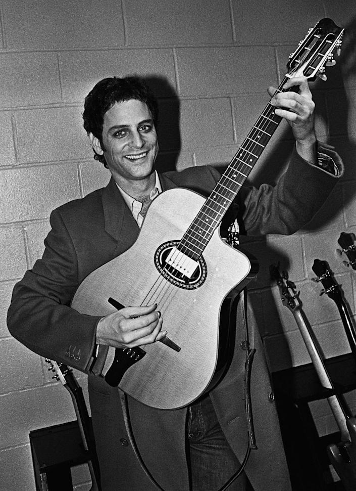 <p>Prior to a 1979 concert, Fleetwood Mac guitarist Lindsey Buckingham poses with one of his many guitars backstage. </p>