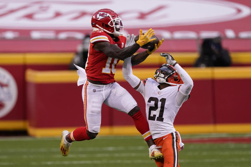 Kansas City Chiefs wide receiver Tyreek Hill makes a catch over Cleveland Browns cornerback Denzel Ward (21) during the second half of an NFL divisional round football game, Sunday, Jan. 17, 2021, in Kansas City. (AP Photo/Charlie Riedel)
