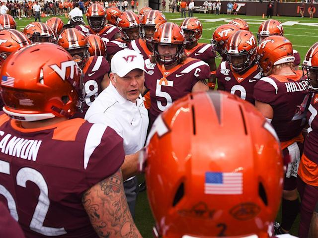 <p>Virginia Tech head coach Justin Fuente speaks to his team inside a huddle prior to the game against the Furman Paladins at Lane Stadium on Sept. 14, 2019.</p>