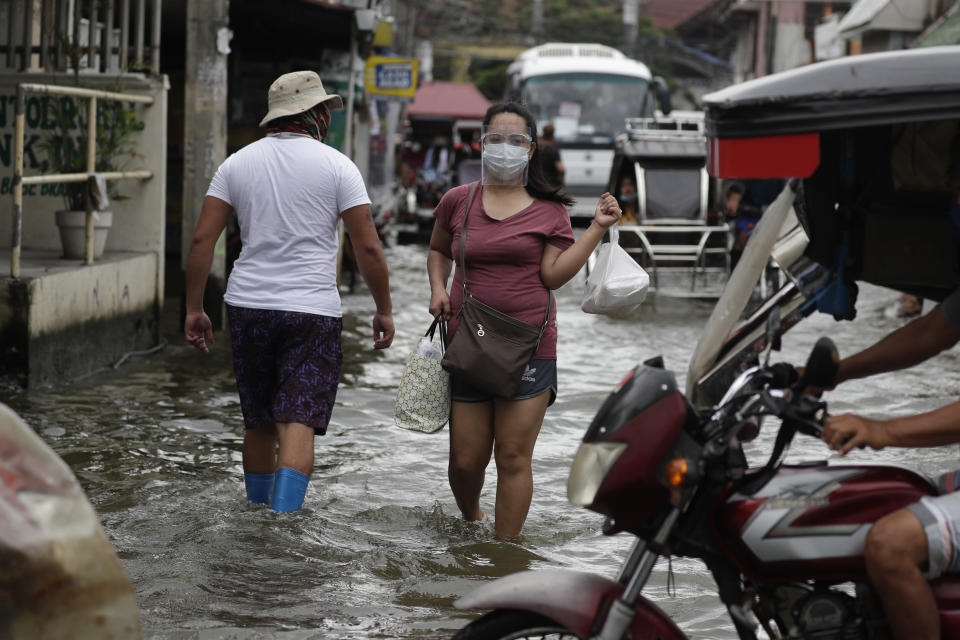 A woman wearing masks to prevent the spread of the coronavirus wades along a flooded road due to Typhoon Molave in Pampanga province, northern Philippines on Monday, Oct. 26, 2020. A fast moving typhoon has forced thousands of villagers to flee to safety in provinces. (AP Photo/Aaron Favila)