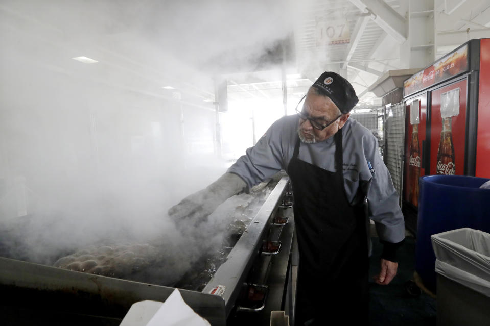 A sous chef, who declined to be identified, sends up a cloud of smoke as he cleans his ballpark concession grill after the cancellation of the sprint training baseball game between the Kansas City Royals and the Seattle Mariners Thursday, March 12, 2020, in Surprise, Ariz. Major League Baseball is delaying the start of its season by at least two weeks because of the coronavirus outbreak and has suspended the rest of its spring training game schedule. (AP Photo/Elaine Thompson)