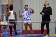 FILE - In this May 11, 2021, file photos, gymnast Jordan Chiles, center, talks with coach Cecile Landi, right and reigning Olympic champion gymnast Simone Biles, left, while training in Spring, Texas. The 20-year-old Chiles will compete at the U.S. Championships this weekend hoping to build off a strong performance at the U.S. Classic, where she finished second to Olympic and world champion Simone Biles. (AP Photo/David J. Phillip, File)