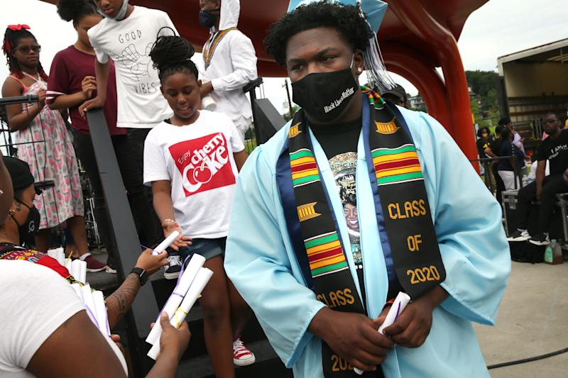 SEATTLE, WA - JUNE 19: Diplomas made by event organizers are handed to recent graduates as they depart the stage during the Juneteenth Freedom March and Celebration on June 19, 2020 in Seattle, Washington. Juneteenth commemorates June 19, 1865, when a Union general read orders in Galveston, Texas stating all enslaved people in Texas were free according to federal law. (Photo by Karen Ducey/Getty Images)