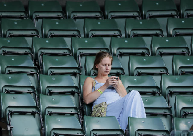 A spectator looks at her mobile phone while attending the men's singles quarterfinal tennis match between John Isner of the United States and Canada's Milos Raonic, at the Wimbledon Tennis Championships, in London, Wednesday July 11, 2018. (AP Photo/Ben Curtis)