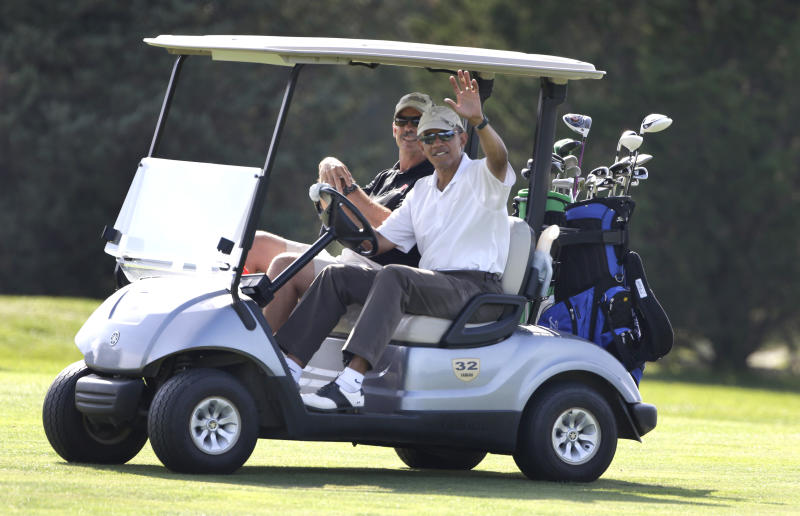 CORRECTS FIRST NAME TO GLENN-President Barack Obama, right, waves to a crowd of on-lookers while driving a golf cart with businessman Glenn Hutchins, behind, as they golf at Farm Neck Golf Club in Oak Bluffs, Mass., on the island of Martha's Vineyard, Saturday, Aug. 17, 2013. (AP Photo/Steven Senne)