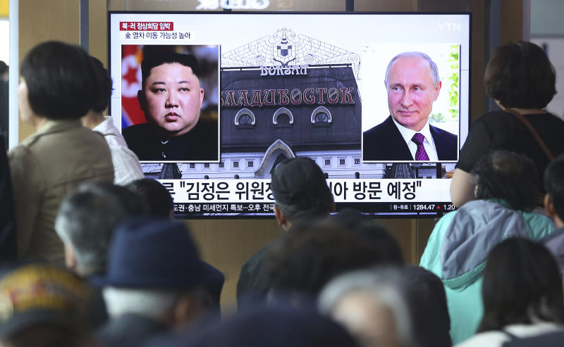 """People watch a TV screen showing images of North Korean leader Kim Jong Un, left, and Russian President Vladimir Putin, right, during a news program at the Seoul Railway Station in Seoul, South Korea, Tuesday, April 23, 2019. North Korea confirmed Tuesday that Kim will soon visit Russia to meet with Putin in a summit that comes at a crucial moment for tenuous diplomacy meant to rid the North of its nuclear arsenal. The Korean letters on the screen read:: """"Kim Jong Un plans to visit Russia ."""" (AP Photo/Ahn Young-joon)"""