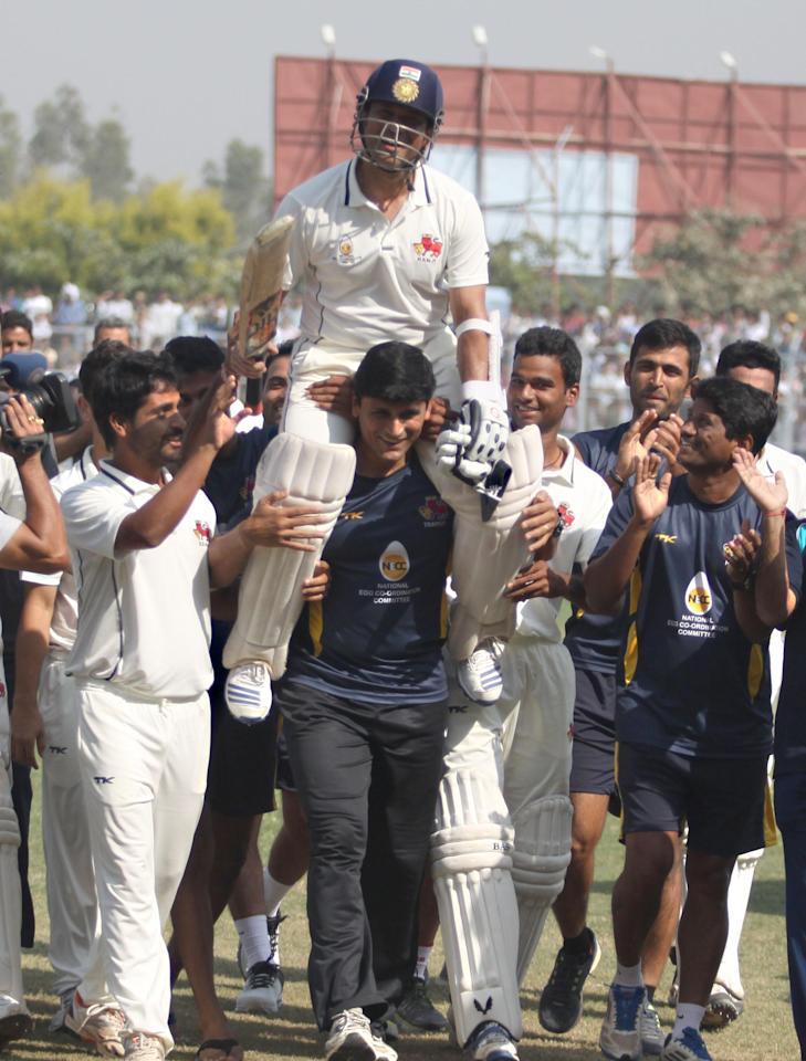 Players lift master blaster Sachin Tendulkar after Mumbai won the Ranji Trophy match between Haryana and Mumbai played at Bansi Lal Cricket Stadium in Rohtak on Oct.30, 2013. This was Sachin's farewell game in domestic cricket. (Photo: IANS)