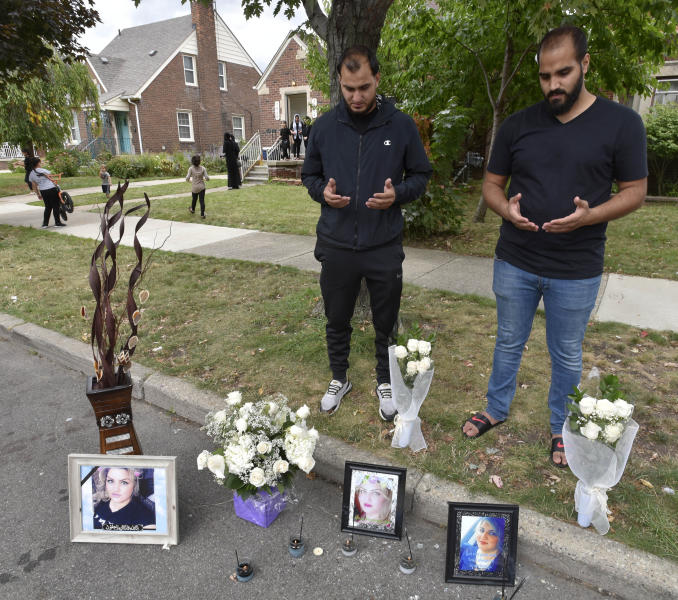 Mohammad Aljanabi, left, and Ali Aljanabi, brothers of shooting victim, Saja Aljanabi, says prayers at their sister's memorial Sunday, Sept. 8, 2019, as they light candles around her memorial  in Dearborn, Mich.  Dearborn Police Chief Ronald Haddad said Thursday, Sept. 12, 2019, that the 14-year-old, a 13-year-old and 17-year-old are being held in connection with last week's killing of Saja Aljanabi and they could be involved in other crimes in the area. (Todd McInturf/Detroit News via AP)