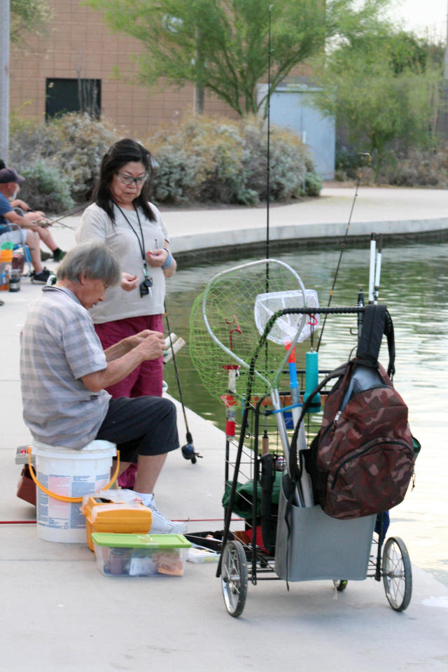 In this April, 30, 2020 photo, a couple sets up their lines to fish at Veterans Oasis Park in Chandler, Ariz. Fishing at community lakes has become a popular outdoor activity for people who have been locked up in their homes during the coronavirus pandemic. Many state fishing have continued to stock lakes during the outbreak. (AP Photo/John Marshall)