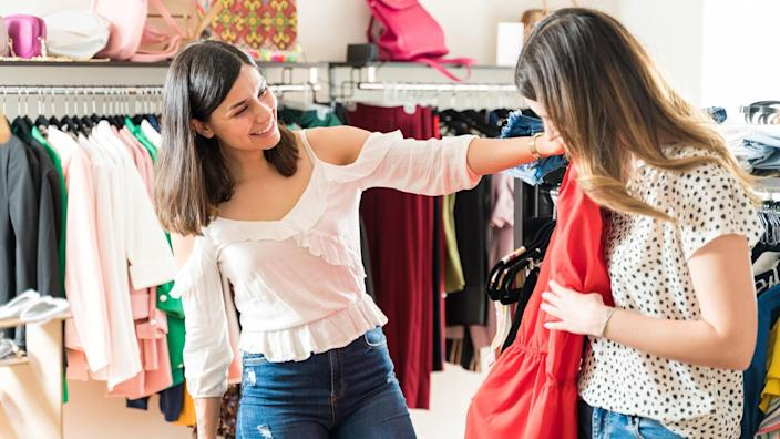 Pretty woman suggesting red top for friend while shopping in boutique.