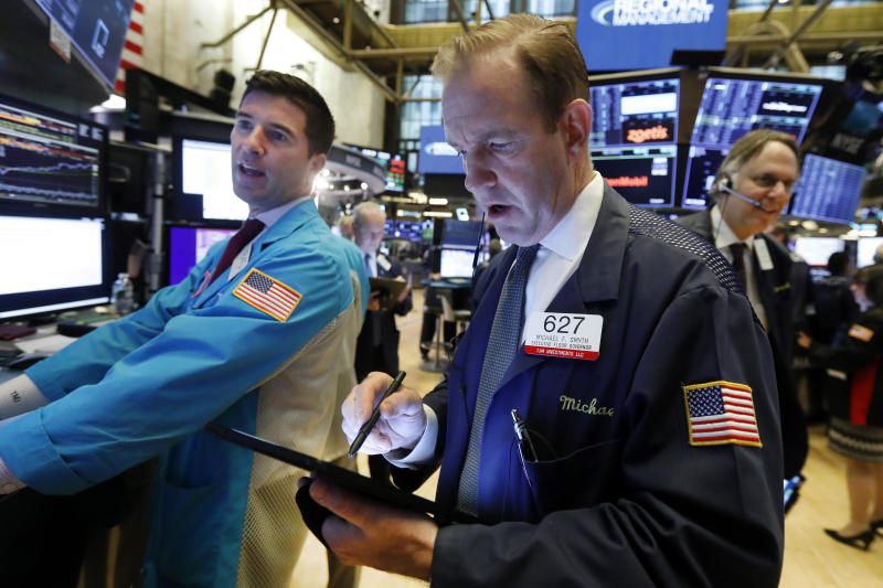 Specialist Thomas McArdle, left, and trader Michael Smyth, center, work on the floor of the New York Stock Exchange, Wednesday, Oct. 30, 2019. Stocks are slipping in early trading on Wall Street as traders hold back ahead of an interest rate announcement from the Federal Reserve. (AP Photo/Richard Drew)