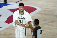 FILE - Milwaukee Bucks' Giannis Antetokounmpo (34) fist bumps referee James Capers (19) after an NBA basketball first-round playoff game against the Orlando Magic Monday, Aug. 24, 2020, in Lake Buena Vista, Fla. Safety is the primary reason why the status of the fist bump elevated big-time in 2020. The handshake was simply a causality of the coronavirus. (AP Photo/Ashley Landis, Pool, File)