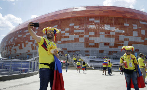 Fans take pictures in front of the stadium prior to the group H match between Colombia and Japan at the 2018 soccer World Cup in the Mordavia Arena in Saransk, Russia, Tuesday, June 19, 2018. (AP Photo/Mark Baker)