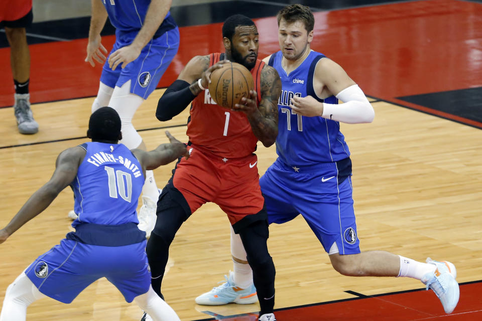Houston Rockets guard John Wall (1) drives between Dallas Mavericks forward Dorian Finney-Smith (10) and guard Luka Doncic (77) during the first half of an NBA basketball game Wednesday, April 7, 2021, in Houston. (AP Photo/Michael Wyke, Pool)